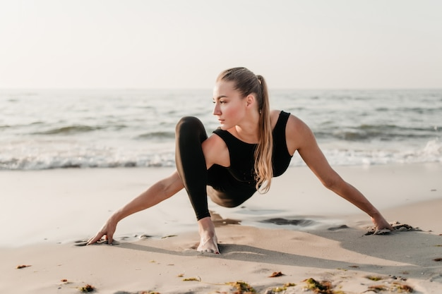 Молодая подходящая женщина практикует йогу асаны на песке у океана