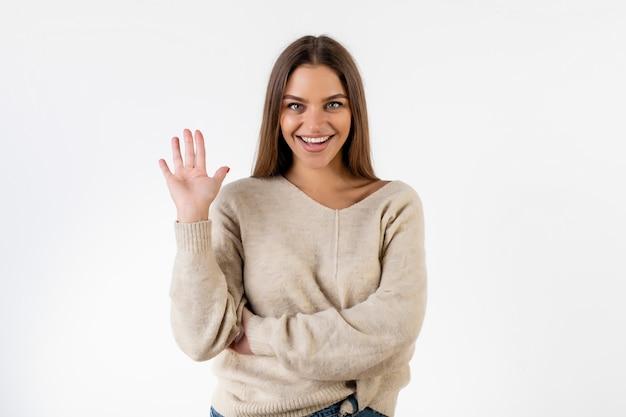 Дружественные красивая женщина, поднимая руку, говорю привет, изолированные на белом
