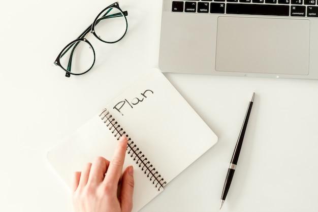 Запись плана в тетради с копией пространства. бизнес-концепция - работа в ярком современном офисе