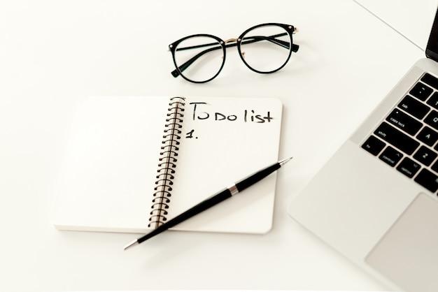 Написание плана работы в тетради возле ноутбука на столе в офисе