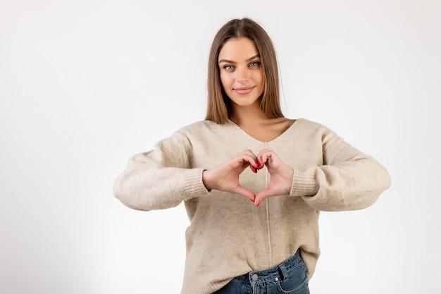 Шаловливая женщина показывая жест сердца с руками изолированными над белизной