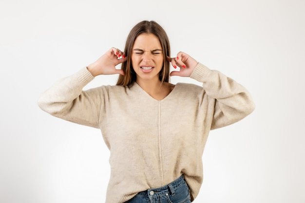 Раздраженная женщина закрывает уши пальцами, изолированными над белым