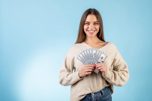 Счастливый красивая женщина, держащая кучу денег сто долларовых купюр, изолированных на синем