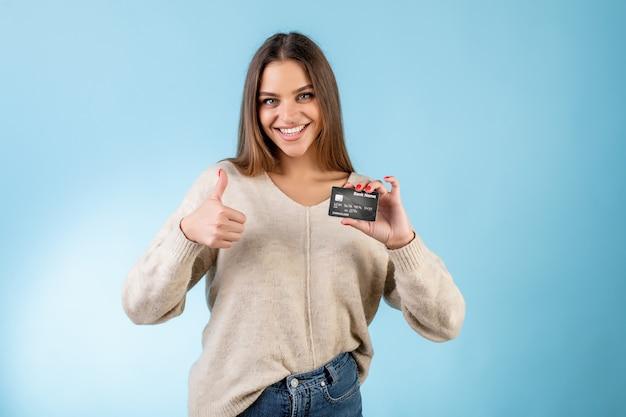 Жизнерадостная женщина держа кредитную карточку и показывая большие пальцы руки вверх изолированные над синью