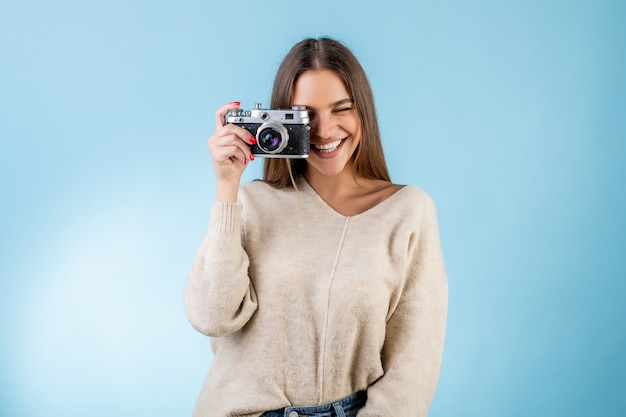 Красивая женщина, делая картину с марочных фотоаппарат, изолированных на синий
