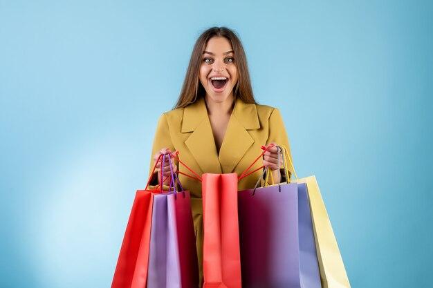Счастливая женщина раскрывая красные красочные хозяйственные сумки изолированные над синью