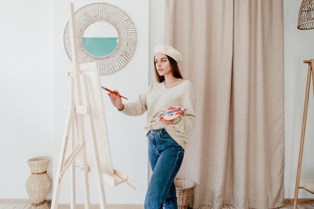 Красивая художница женщина рисует картину на холсте в мастерской