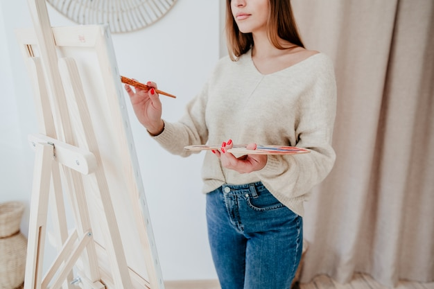 Обрезанный снимок женщины художника рисования картины с яркими цветами на холсте в мастерской студии