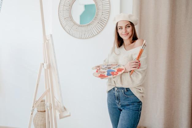 ワークショップスタジオで笑みを浮かべて手でパレットとブラシと明るい色でキャンバスに絵を描く美しいアーティスト女性