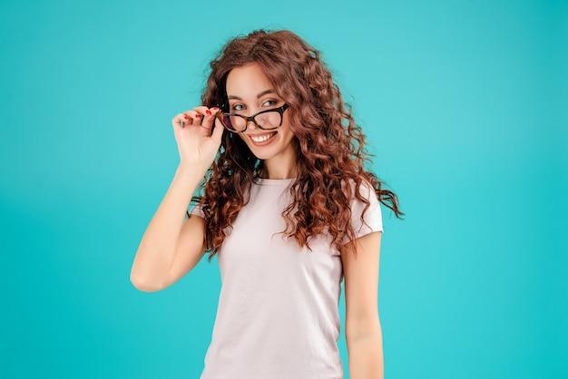 ターコイズブルーの背景に分離されたビジョンのメガネと笑顔の女性