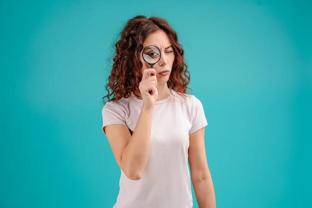 分離された虫眼鏡を通して密接に見ている女性を集中