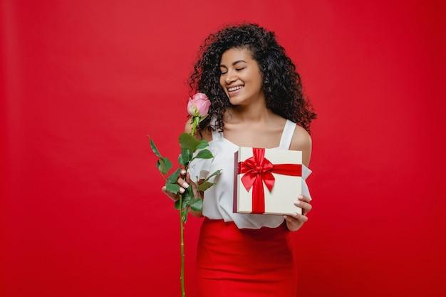 Довольно черная женщина пахнущие розовые розы с валентина подарок, изолированных на красный