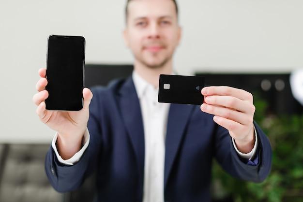 クレジットカードと携帯電話を持ったビジネスマン