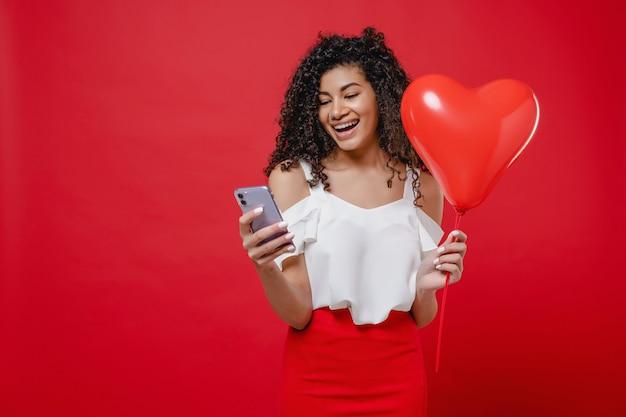 Чернокожая женщина улыбается и смотрит на телефон с воздушным шаром в форме сердца на красной стене