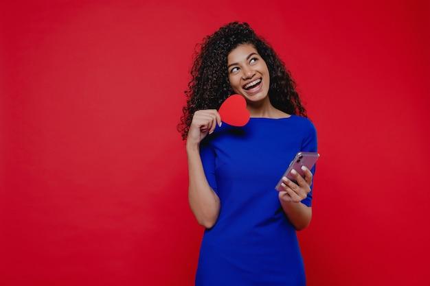 Красивая негритянка с сердцем в форме валентина карты, глядя на телефон на красной стене
