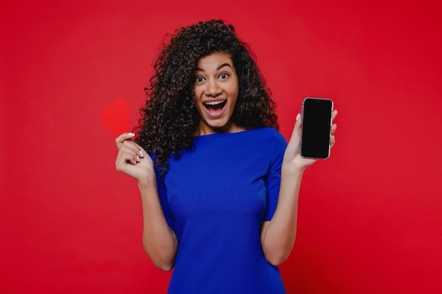 Чернокожая женщина показывая телефон с пустым экраном космоса экземпляра и валентинкой в форме сердца на красной стене