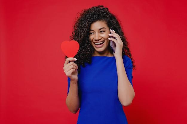 Черная женщина с форме сердца валентина карты разговаривает по телефону на красной стене