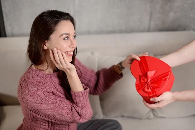 Девушка получает подарочную коробку в форме сердца из рук своего парня