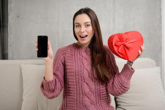 Красивая девушка в костюме держит подарочную коробку в форме сердца и мобильный телефон с пустым экраном
