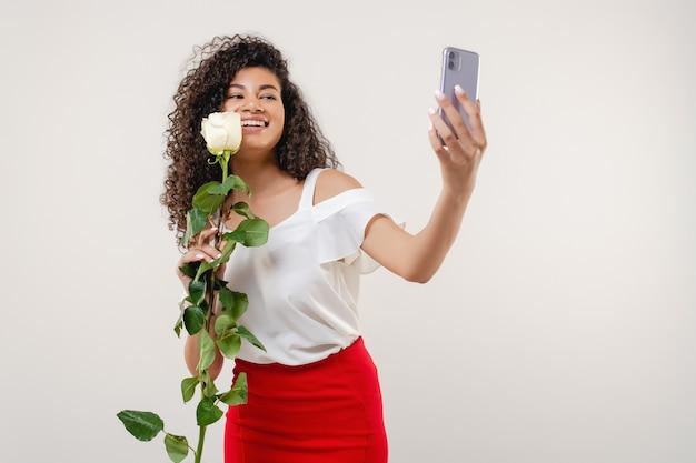Чернокожая женщина делает селфи с розой в красной юбке и белой блузке