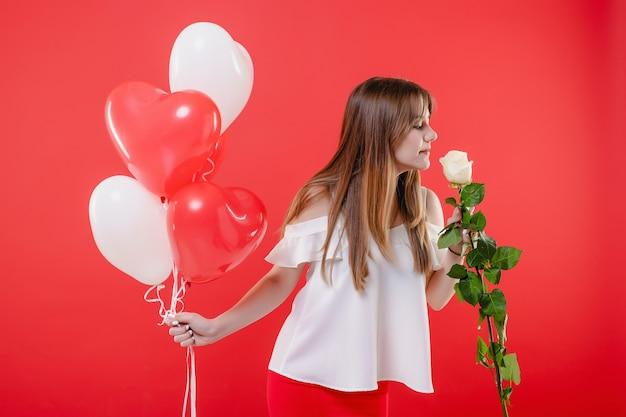 Женщина пахнущие белые розы и воздушные шары в форме сердца, изолированные на красной стене