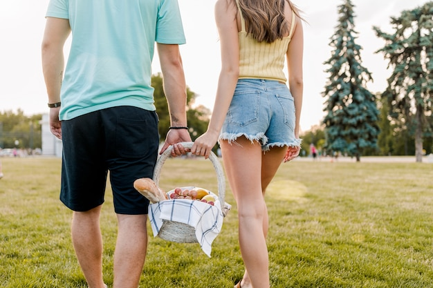 ロマンチックなカップルは公園でフルーツピクニックバスケットを持って
