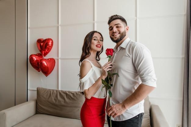 男と女のアパートでハート形の風船を自宅で赤いバラと