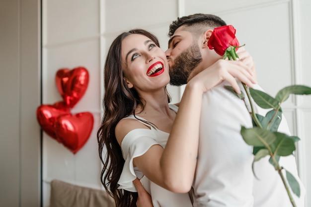 Мужчина и женщина с красной розой дома с воздушными шарами в форме сердца в квартире