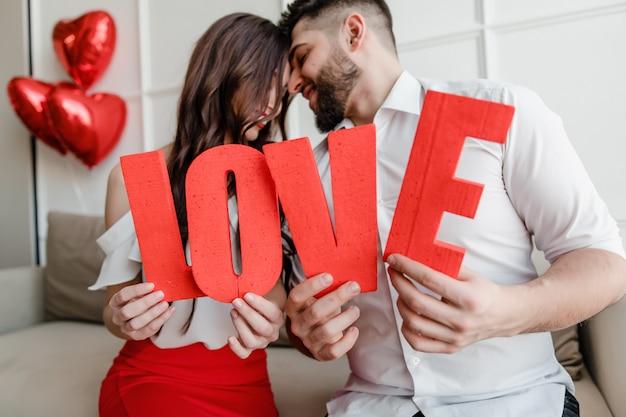 男と女の自宅でソファに座ってハート形風船と赤いラブレターを保持