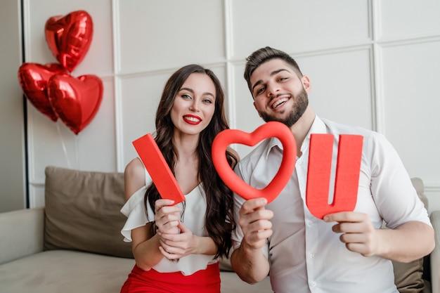 Пара парень и девушка с красным я люблю тебя письма и воздушные шары в форме сердца у себя дома на диване