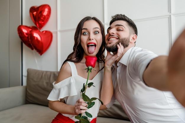 Красивая пара мужчина и женщина делает селфи с красной розой и воздушными шарами в форме сердца у себя дома на диване