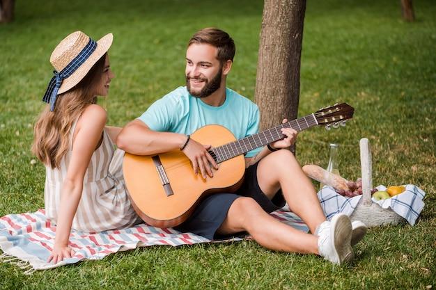 男は日没の夏に公園でピクニックに彼のガールフレンドのためにギターを弾く