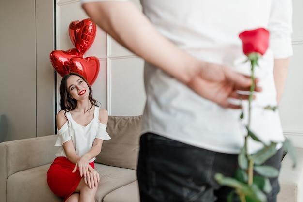 Человек с розой в руке делает сюрприз для женщины, сидя на диване с воздушными шарами в форме сердца у себя дома
