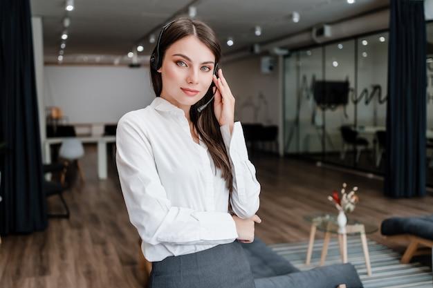 コールセンターのオペレーターとしての女性はオフィスで働いており、ヘッドセットを介して電話で話しています