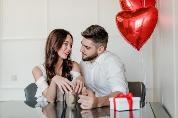 カップルの男性と女性の朝のカップから飲むギフトボックスと自宅でハート形の風船でプレゼント