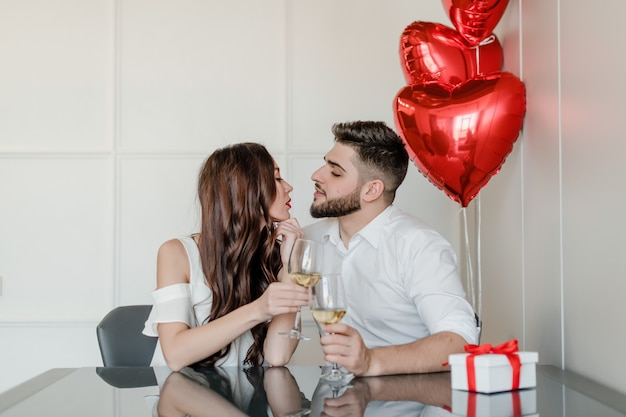 幸せなハンサムな男と女は、自宅でギフトボックスと赤いハート形の風船をプレゼントで自宅で白ワインを飲む