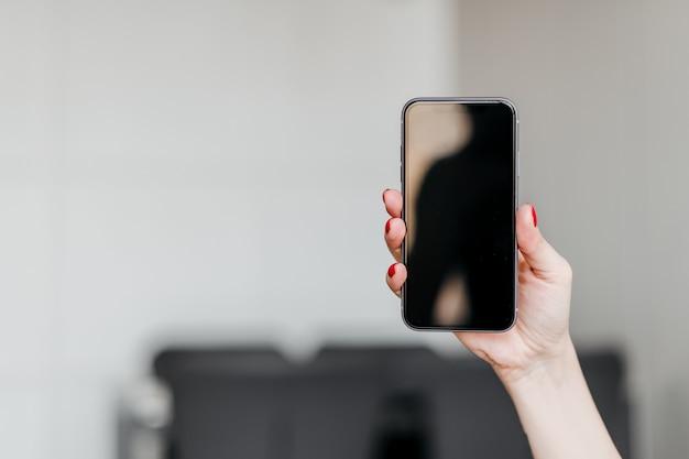 自宅のアパートでコピースペース空白の空の画面で新しい携帯電話を持っている女性の手