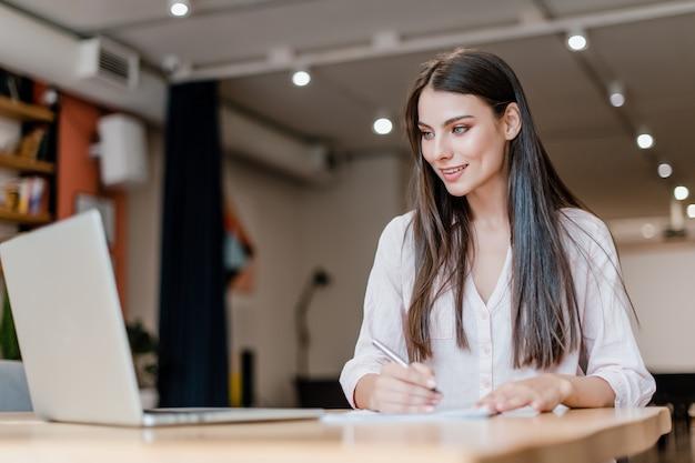 ビジネスの女性のラップトップでオフィスで働くと論文に署名する