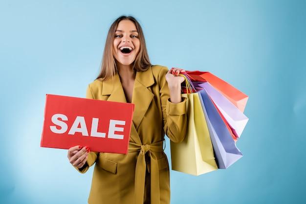 Красивая усмехаясь женщина держа красный знак продажи и красочные хозяйственные сумки