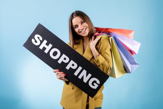 Красивая женщина, держащая черный торговый знак и красочные сумки