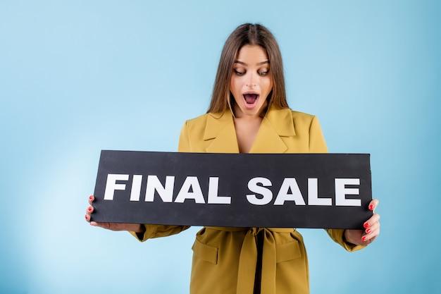 Красивая женщина, держащая черный окончательный знак продажи, изолированные над синим