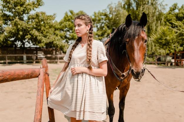 牧場で馬と田舎娘