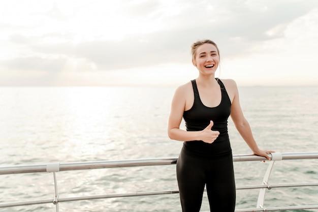 笑みを浮かべて、ジョギング後に親指を現してビーチで女性