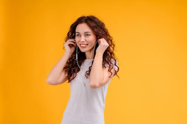 魅力的な女の子は黄色の背景に分離された耳ポッドを介して音楽を聴きます