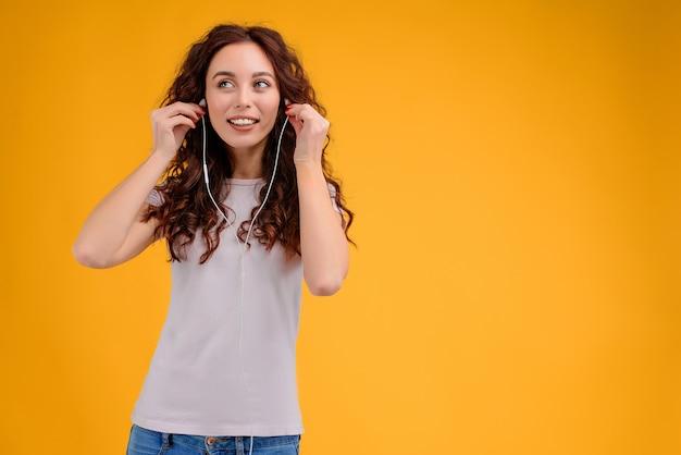 幸せな女黄色の背景に分離された耳ポッドを介して音楽を聴く