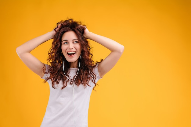 幸せな女ダンスと黄色の背景に分離された耳ポッドから音楽を聴く