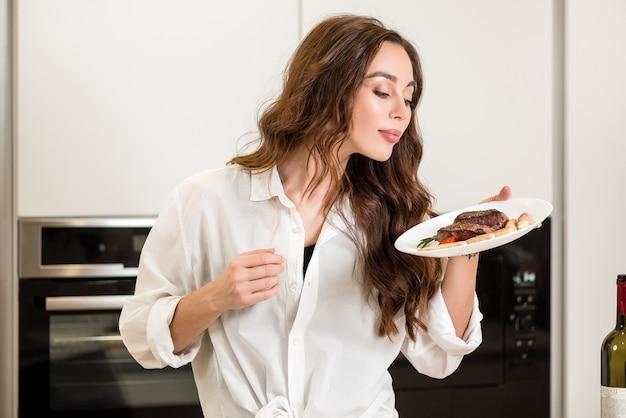 自宅のキッチンで揚げ肉料理を持つ女性