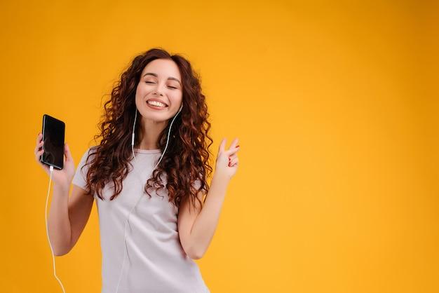 笑顔の女性は彼女の電話と黄色の背景に分離された耳のさやから音楽を聴きます
