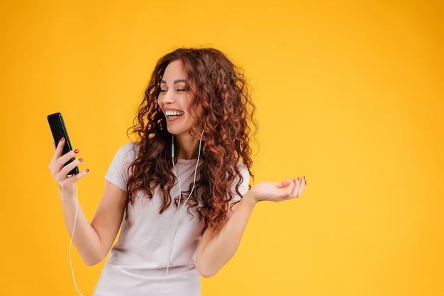 黄色の背景に分離された電話と耳のさやで笑う女性