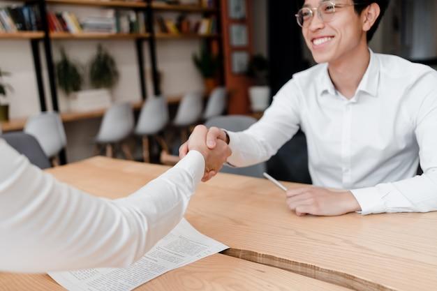 アジア系のビジネスマンが契約に手を振る